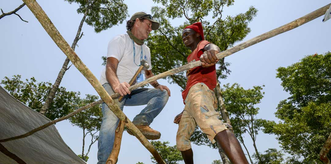 UNHCR shelter expert Tom Corcoran helps a refugee construct a temporary home in Tanzania